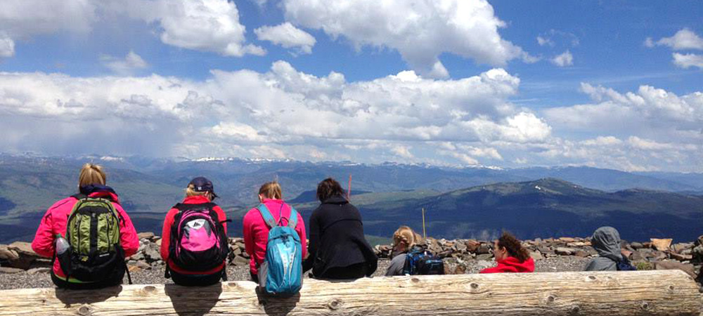 Students sit on top of a log that overlooks a view of mountains