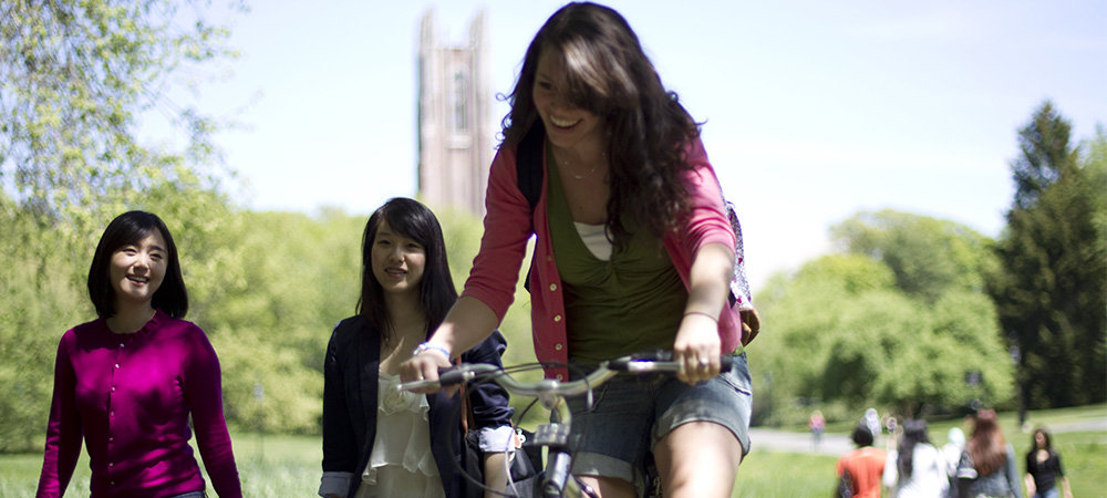 student biking through campus